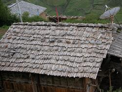 Rocks to hold roof slats on, but still has a satellite dish!
