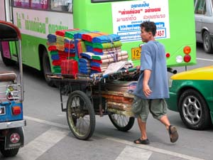Bangkok, Thailand - Street Vendor Weaving Through Traffic