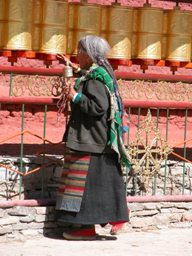 Elderly woman with prayer beads and prayer wheel, spinning larger prayer wheels