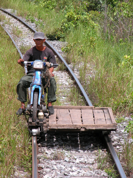 Motorcycle to Haul Lumber to the Rear of the Moving Train, where Workers Hoisted it onto the Roof of the Train